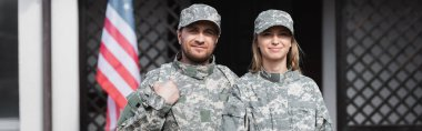 Smiling military couple looking at camera on blurred background, banner stock vector