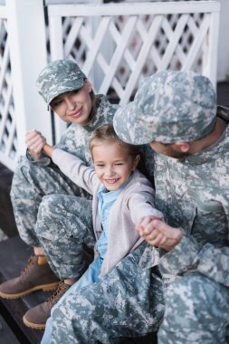 Happy military father and mother with daughter sitting on house threshold on blurred background stock vector