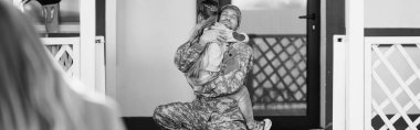 Father in military uniform embracing daughter, while sitting on knee  near back door with blurred woman on foreground, banner, monochrome stock vector