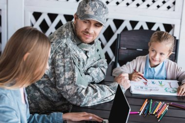 Smiling man in military uniform looking at woman typing on laptop, while sitting with daughter drawing at table stock vector