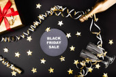 Top view of round with black friday sale lettering near bottle of champagne, gift and festive decor on black background