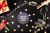 Top view of round with black friday sale lettering near festive decor, bottle of champagne and gift on black background