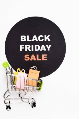Top view of toy shopping cart with bags and circle with black friday sale on white background stock vector