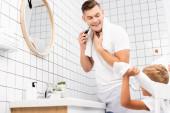 Boldog apa borotválkozás elektromos borotvával és nézi fiát ül a széken a fürdőszobában