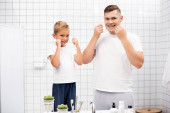 Smiling father and son looking at camera while cleaning teeth with dental floss near sink in bathroom