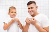 Usmívající se otec a syn tahání bílé trička při pohledu na kameru v koupelně