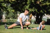 Usmívající se mladý dospělý muž dělá výpady při pohledu na chlapce ve sportovním oblečení na rozmazaném pozadí