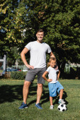 Smiling father with hands on hips with looking at camera with smiling son standing with leg on ball in park