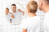 Cheerful father and son brushing teeth while looking at mirror in bathroom on blurred foreground