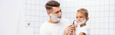 Smiling father looking at son with shaving foam on face holding safety razor near cheek in bathroom, banner