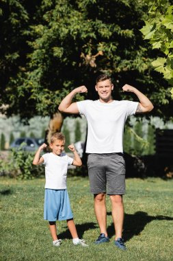 Smiling father and son in sportswear looking at camera, while showing raised hands with blurred park on background stock vector