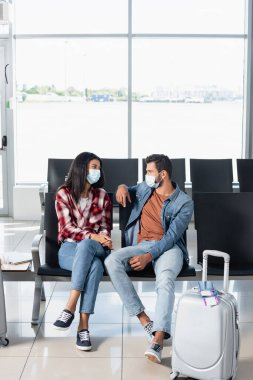 Interracial couple in medical masks sitting and looking at each other near luggage in departure lounge stock vector