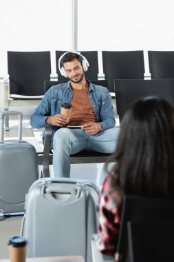 bearded man in headphones holding paper cup near luggage and woman on blurred foreground