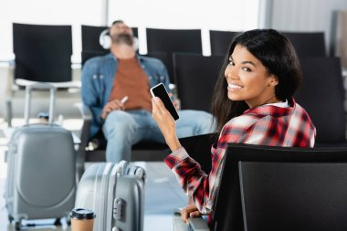 happy african american woman holding smartphone with blank screen near luggage and man on blurred background