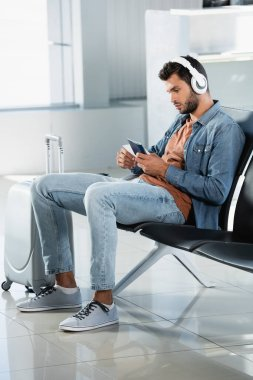 man in headphones holding passport in departure lounge of airport