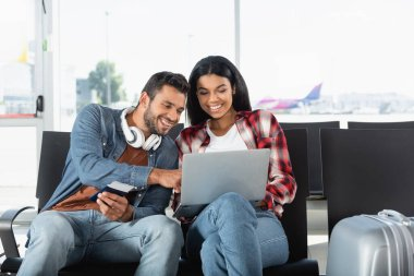 happy interracial couple looking at laptop in airport
