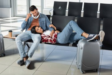 Happy african american woman lying near cheerful man in departure lounge of airport stock vector