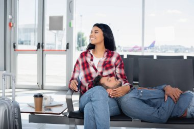 Bearded man lying near happy african american woman in departure lounge of airport stock vector