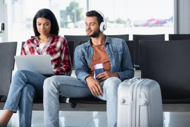 bearded man listening music and looking at laptop near african american woman in airport