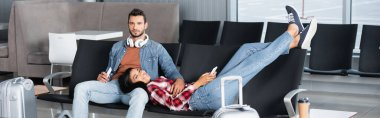 happy african american woman holding phone and lying on bearded man in departure lounge, banner