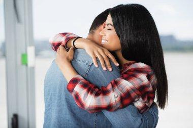 Happy african american woman hugging boyfriend in airport stock vector