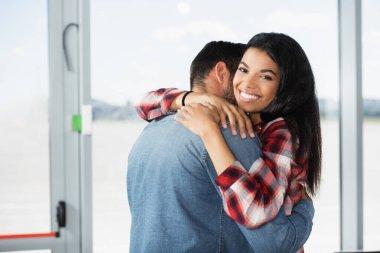 Cheerful african american woman hugging boyfriend in airport stock vector
