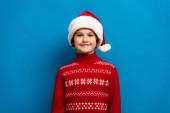 glücklicher Junge mit Weihnachtsmütze und rotem Pullover, der auf blauem Grund in die Kamera blickt