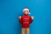 fröhliches Kind mit Weihnachtsmütze und rotem Pullover, das Daumen hoch zeigt, während es in die Kamera auf blau blickt