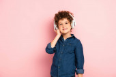 pleased boy listening music and touching wireless headphones on pink