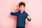 joyful and curly boy listening music in wireless headphones while showing thumb up on pink