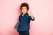 joyful boy holding laptop and showing thumb up on pink