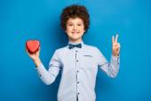 potěšený chlapec drží červené srdce ve tvaru krabice a ukazuje mír znamení na modré