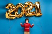 curly boy in red sweater showing thumbs up near near golden balloons with 2021 numbers on blue