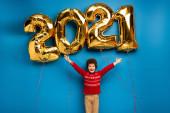 izgatott fiú piros pulóverben áll kinyújtott kézzel közel arany lufik 2021 számok kék