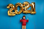 Aufgeregter Junge im roten Pullover zeigt mit den Fingern auf goldene Luftballons mit den Zahlen 2021 auf blauem Grund
