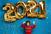 Photo excited boy in red sweater gesturing near golden balloons with 2021 numbers and confetti on blue