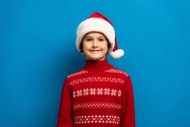 Happy boy in santa hat and red sweater looking at camera on blue stock vector