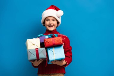 Joyful boy in santa hat and sweater holding presents on blue stock vector