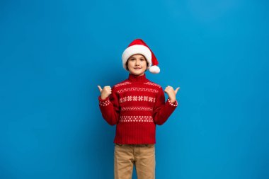 Joyful kid in santa hat and red sweater showing thumbs up while looking at camera on blue stock vector