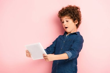 Surprised and curly kid using digital tablet on pink stock vector
