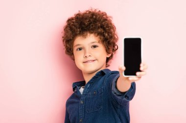 Selective focus of curly boy in denim shirt holding smartphone with blank screen on pink stock vector
