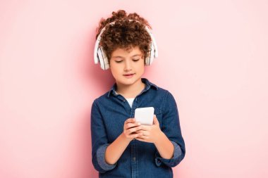 curly boy listening music in wireless headphones and using smartphone on pink