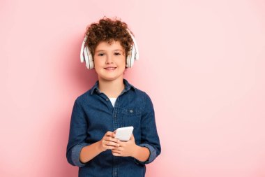 Joyful and curly boy listening music in wireless headphones and holding smartphone on pink stock vector