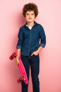 Curly boy holding penny board and standing with hand in pocket on pink stock vector