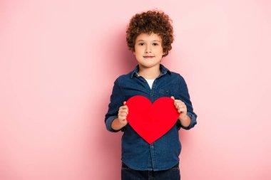 Joyful boy holding heart shape paper cut on pink stock vector