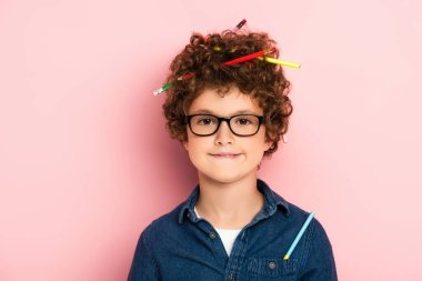 Pleased kid in glasses with color pencils in curly hair on pink stock vector