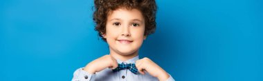 Horizontal crop of curly kid in shirt touching bow tie and smiling on blue stock vector