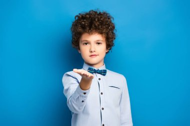 Curly kid in shirt and bow tie pointing with hand and looking at camera on blue stock vector