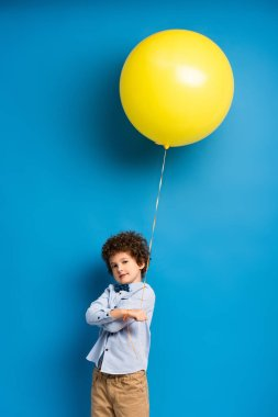 Curly boy in shirt and bow tie holding yellow balloon on blue stock vector