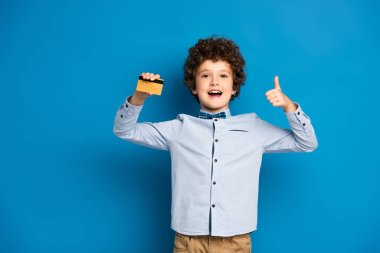 Excited boy holding credit card and showing thumb up on blue stock vector